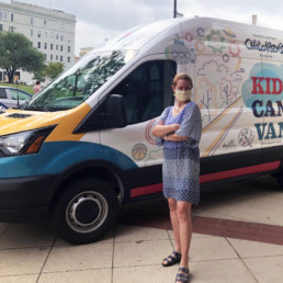Maggie Lancaster, GRCM CEO, in front of the van.