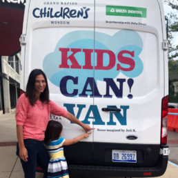 Jodi Rector, winner of the GRCM contest to name the van, pointing to her name on the back of the van.