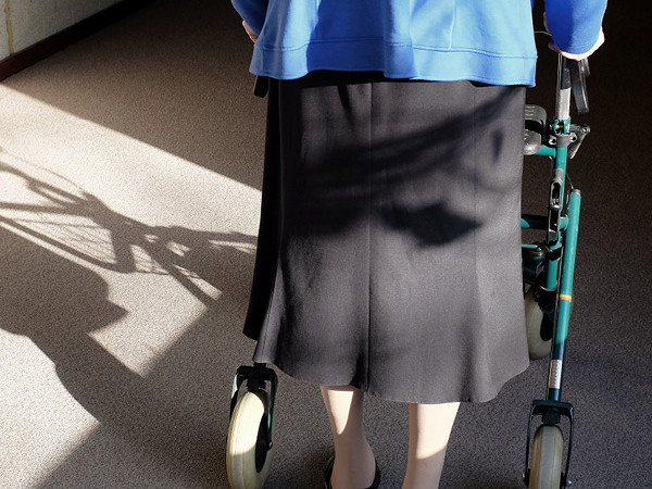 Elderly woman walking way form camera